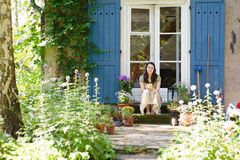 Woman in the garden. Young woman sitting in the sun in her garden Royalty Free Stock Photo