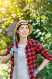 Woman gardener holding spade. Young woman gardener holding spade in sunshine garden. People, gardening, planting, hobby concept Stock Images