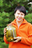 Woman-gardener holds jar with cucumber Stock Photography