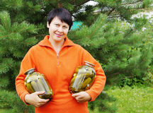 Woman-gardener holds two jars with cucumber Stock Images