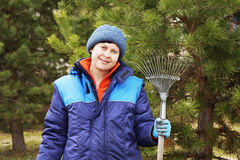 Woman gardener stands with a rake in the garden next to tree Stock Image