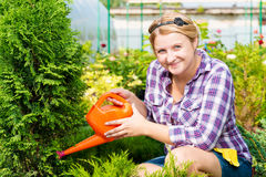 Woman gardener with a watering can watering plants in the nurser Royalty Free Stock Photography