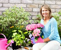 Woman gardening. Smiling happy woman gardening near the home Royalty Free Stock Image