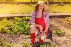 Woman with gardening tool working in garden Stock Photo