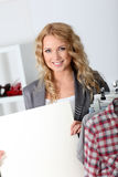 Woman in garment store. Beautiful woman in garment store holding message board stock photography