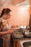 The woman and a gas cooker. Stock Photo