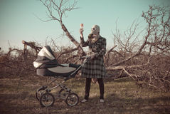 Woman in Gas Mask with Baby Buggy. Child buggy and a mother wearing gas mask, looking at the baby water bottle standing in sorroundings of leavless cutted trees Royalty Free Stock Image