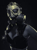 Woman and gas mask. Gloomy atmosphere, woman wearing a gas mask and lingerie - split toning, black and white image, intentional film grain added stock photo