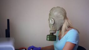 A woman in a gas mask or respirator works at home on a computer. Coronovirus Prevention