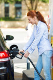 Woman at gas station, filling up her car Stock Images