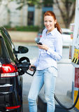 Woman at gas station, filling up her car Stock Photography
