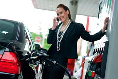 Woman in gas station talking to mobile phone Royalty Free Stock Image