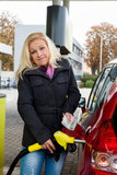 Woman at gas station to refuel. A young woman at a gas station gasoline tank. the cost of the car because of the gas prices are getting more expensive royalty free stock photography
