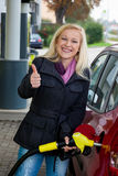 Woman at gas station to refuel stock image