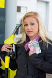 Woman at gas station to refuel. A young woman at a gas station gasoline tank. the cost of the car because of the gas prices are getting more expensive stock photos