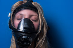 Woman in gasmask. Against dark background Royalty Free Stock Images