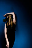 Woman in gasmask. Against dark background Stock Photography