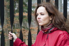 Woman by the gate. Portrait of a woman in red jacket standing by an iron gate; the woman has a thoughtful somewhat sad melancholic expression Stock Photography