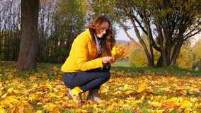 Woman gather bright maple leaves in yellow bunch. Girl looking on sun through bright fallen leaf stock footage