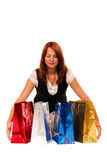 Woman gathering four colored bags. Beautiful woman smiling and gathering four gift bags stock photo