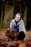 A woman gathering leaves in autumn time Stock Photos