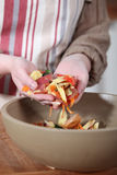 Woman gathering vegetable peelings Royalty Free Stock Photo