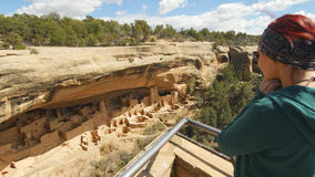 Woman Gazes at Cliff Palace. A woman in a green sweatshirt with a printed headband gazes down at Cliff Palace in Mesa Verde from the observation deck Royalty Free Stock Photography