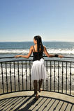 Woman gazing at the sea from deck. Young woman gazing at the ocean Royalty Free Stock Photos