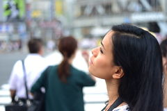 WOMAN GAZING WHILE TRAVELLING. A woman gaze into distance while exploring a new city by herself. Photo taken at the Shibuya Scramble Crossing in Tokyo, Japan stock image