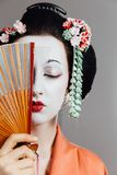 Woman in geisha makeup and a traditional Japanese kimono. Studio, Indoor. Beautiful fan. Hairstyle, flowers in the hair. White face. covers half of the face royalty free stock images