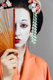 Woman in geisha makeup and a traditional Japanese kimono. Studio, Indoor. Beautiful fan. Hairstyle, flowers in the hair. White face. covers half of the face royalty free stock photo