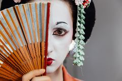 Woman in geisha makeup and a traditional Japanese kimono. Studio, Indoor. Beautiful fan. Hairstyle, flowers in the hair. White face. covers half of the face stock images