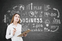Woman generating business idea. Attractive asian woman with clipboard standing on chalkboard background with charts and icons. She is generating business ideas royalty free stock images