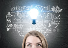 Woman generating business ideas. Portrait of woman looking up at light bulb on chalkboard with financial sketch. She is generating business ideas. Success royalty free stock images