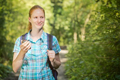 Woman on a Geo-caching Trip. Young female hiker holding an outdoor GPS navigation checks surroundings in a forest Royalty Free Stock Image
