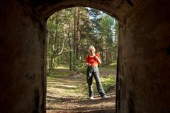 A woman geocaching. Woman holding smartphone while geocaching in abandoned bunker Stock Photo