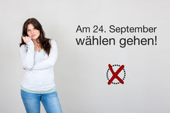 Woman with german appeal to vote at german federal election 2017. Young woman next to appeal in german to go voting during german federal election in September Stock Photo