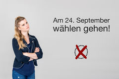 Woman with german appeal to vote at german federal election 2017. Young woman next to appeal in german to go voting during german federal election in September Stock Photos