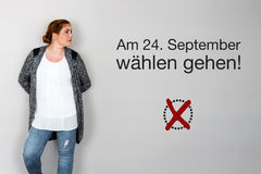 Woman with german appeal to vote at german federal election 2017. Young woman next to appeal in german to go voting during german federal election in September Royalty Free Stock Photo
