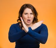 Woman with X gesture to stop talking, cut it out. Portrait angry middle aged woman with X gesture to stop talking, cut it out, dont go there, isolated orange royalty free stock image