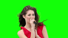 Woman gestures while singing into a microphone Royalty Free Stock Image
