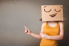 Woman gesturing with a cardboard box Stock Photography