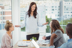 Woman gesturing while discussing with coworkers Royalty Free Stock Photography
