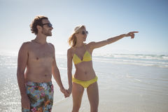 Woman gesturing while holding man hands at beach Royalty Free Stock Image