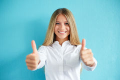 Woman gesturing ok with thumbs up. Smiling young woman gesturing ok with thumbs up, on a blue background Royalty Free Stock Photos
