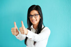 Woman gesturing ok with thumbs up. Young woman gesturing ok with thumbs up, on a blue background Stock Photos