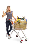 Woman gesturing and posing with shopping cart Royalty Free Stock Photography