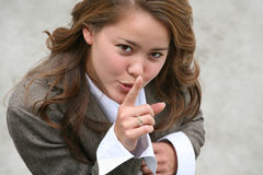 Woman gesturing for quiet. High angle view of attractive young businesswoman with finger to lips gesturing for quiet outdoors Stock Photo