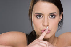 Woman gesturing shhh be quiet big eyes. Portrait of a pretty young girl holding a finger to her mouth, gesturing quiet or silence Stock Photography