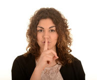 Woman gesturing for quiet. Attractive young woman with her finger to her lips gesturing for quiet, white background Royalty Free Stock Photos